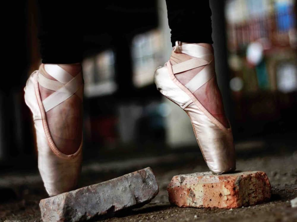 Fitness leggings Ballet shoes on pointe on bricks in studio