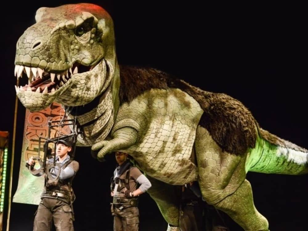 giant dinosaur puppet of a t rex stage show Dinosaur World Live