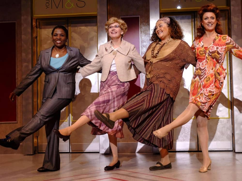 four middle age women sing and dance in Menopause the Musical
