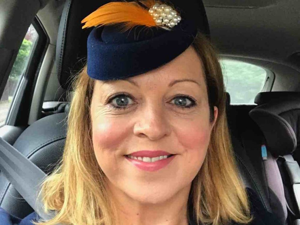 Rachel Jane Muddy Stilettos Editor wearing navy hat and orange feather to Newbury Races