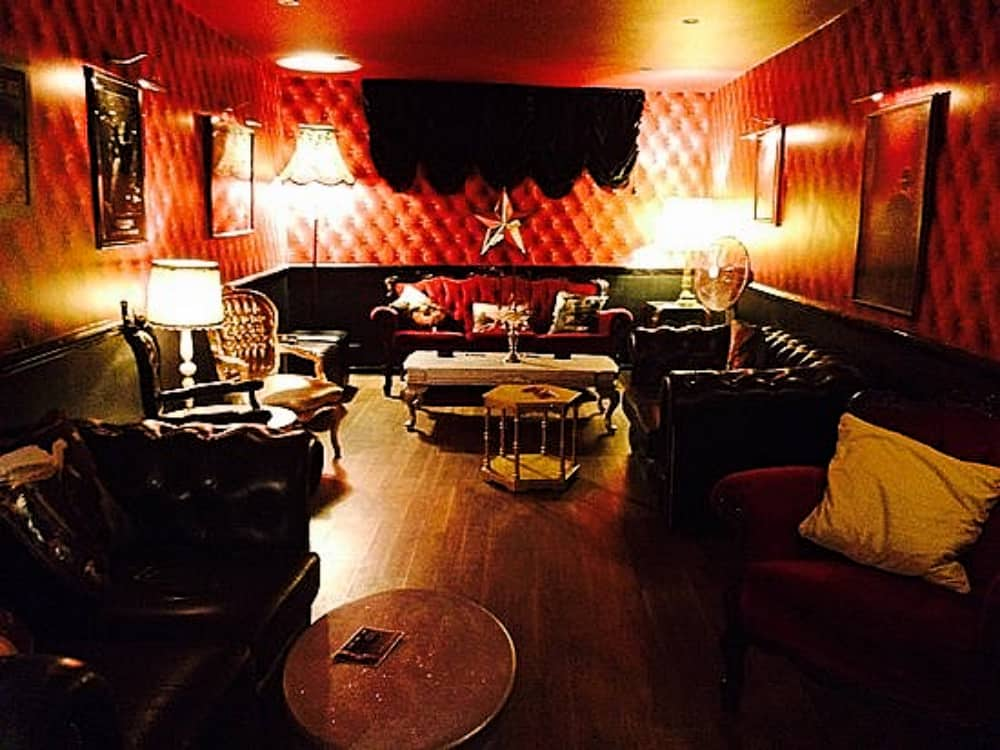 red padded walls and velvet button back sofas in the glam Windsor champagne Bar No5 St Leonard's