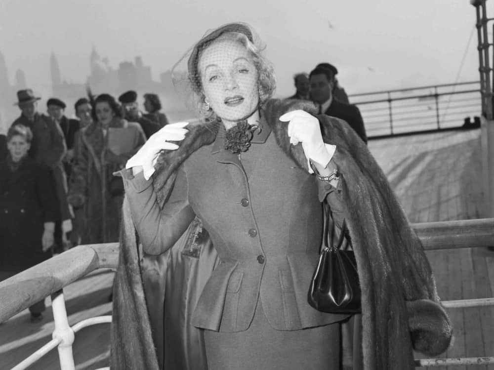 Marlene Dietrich wearing Christian Dior onboard the Queen Elizabeth arriving in New York 1950 V&A Steam and Style Exhibition Getty_Images.