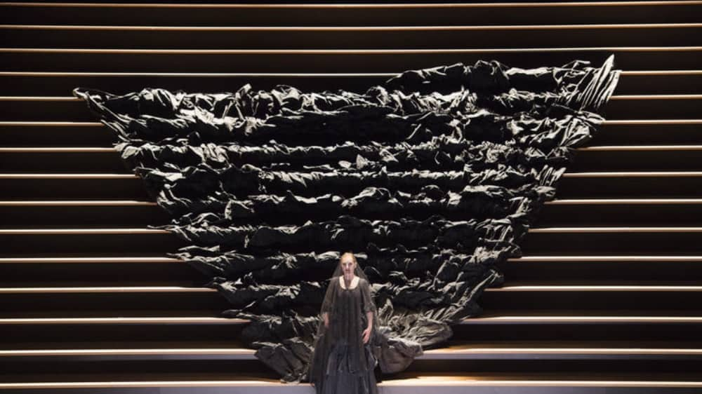 ROH Live Carmen woman walking down steps in black gown with a vast train rippling behind her