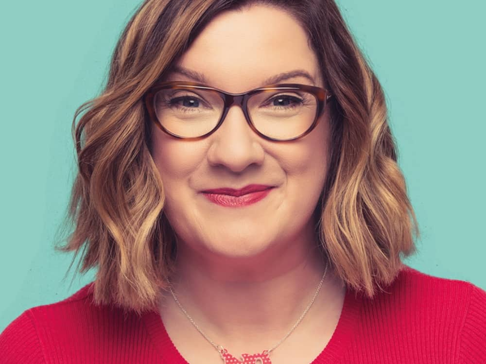 Blonde highlighted bob, red top and tortoiseshell glasses of comedian Sarah Millican
