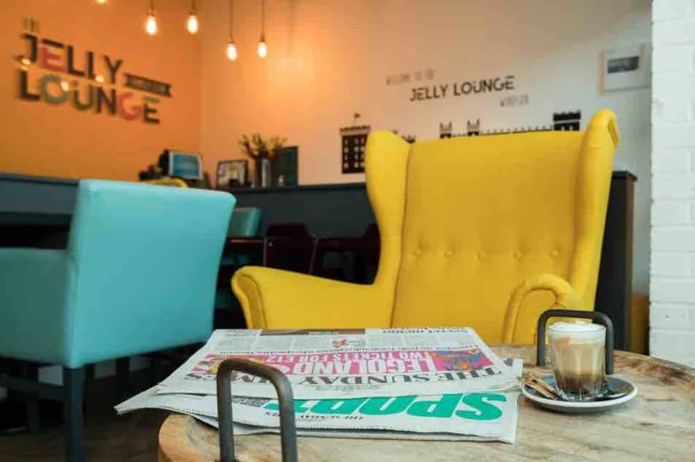 Bright yellow button back chair and turquoise blue sofas at the posh soft play centre The Jelly Lounge