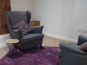 Teal wing backed chairs, vintage tables and purple rug in Therapy room Total Health West BerkshireTherapy Room