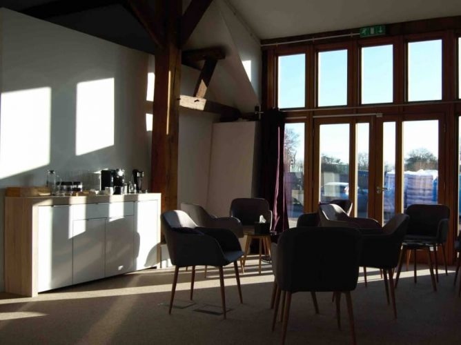 Exposed beams and white walk of Grade II listed barn Total Health West Berkshire