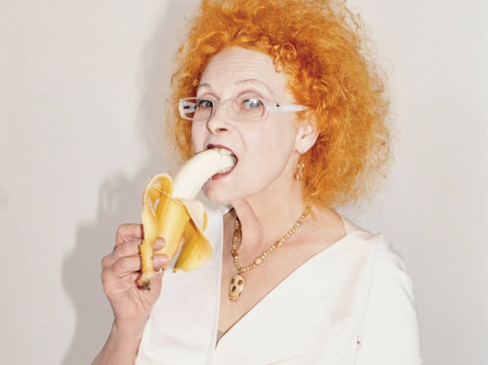 Fashion designer icon punk Vivienne Westwood red curly hair metal rimmed spec eating a banana