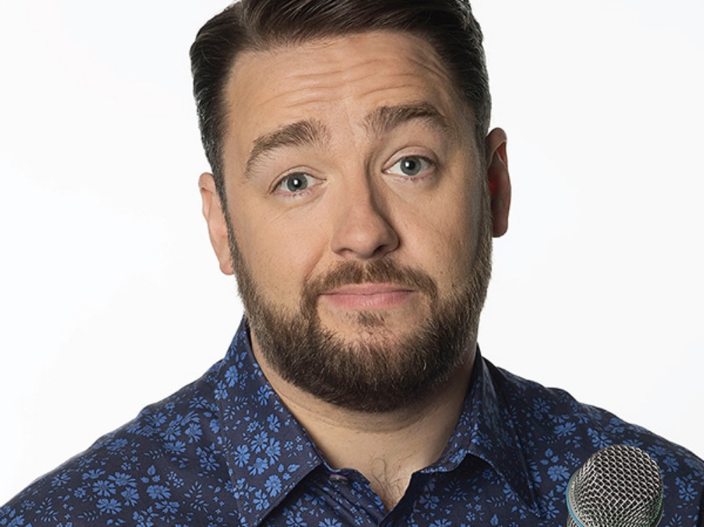 Comedian Jason Manford brown hair bears blue floral shirt holding mic