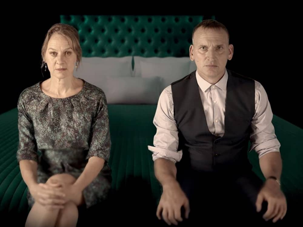 Macbeth RSC Live Christopher Ecclestone and Niamh Cusack sit on an upholstered green bed