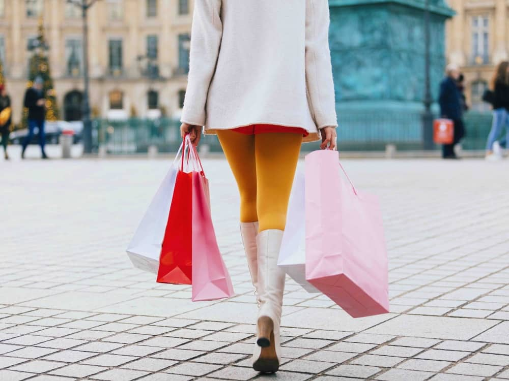 Woman shopping with bad cream short coat knee high boots and mustard yellow tights