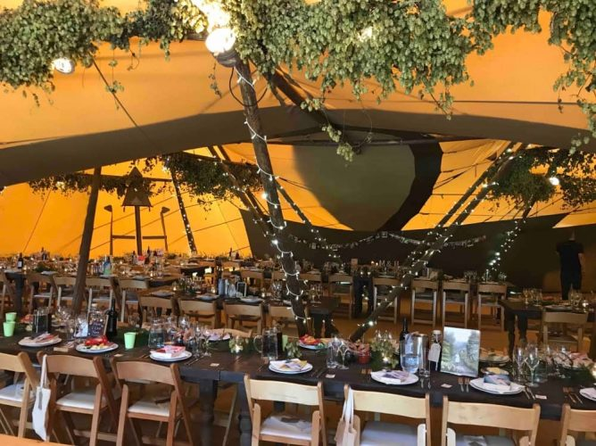 Rustic teepee wedding with wooden chair, trestle tables and hanging greenery – Birch Associates Events