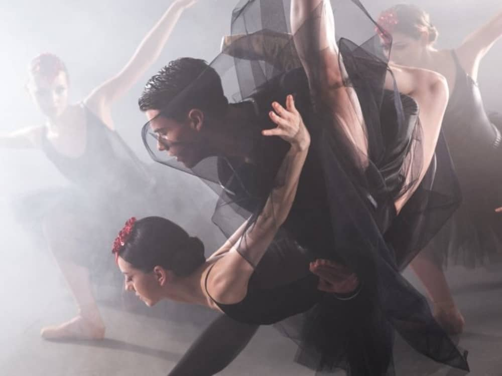 Ballet Centreal Blck Swan dancers wearing black tulle, red hair accessory surrounded by smoke