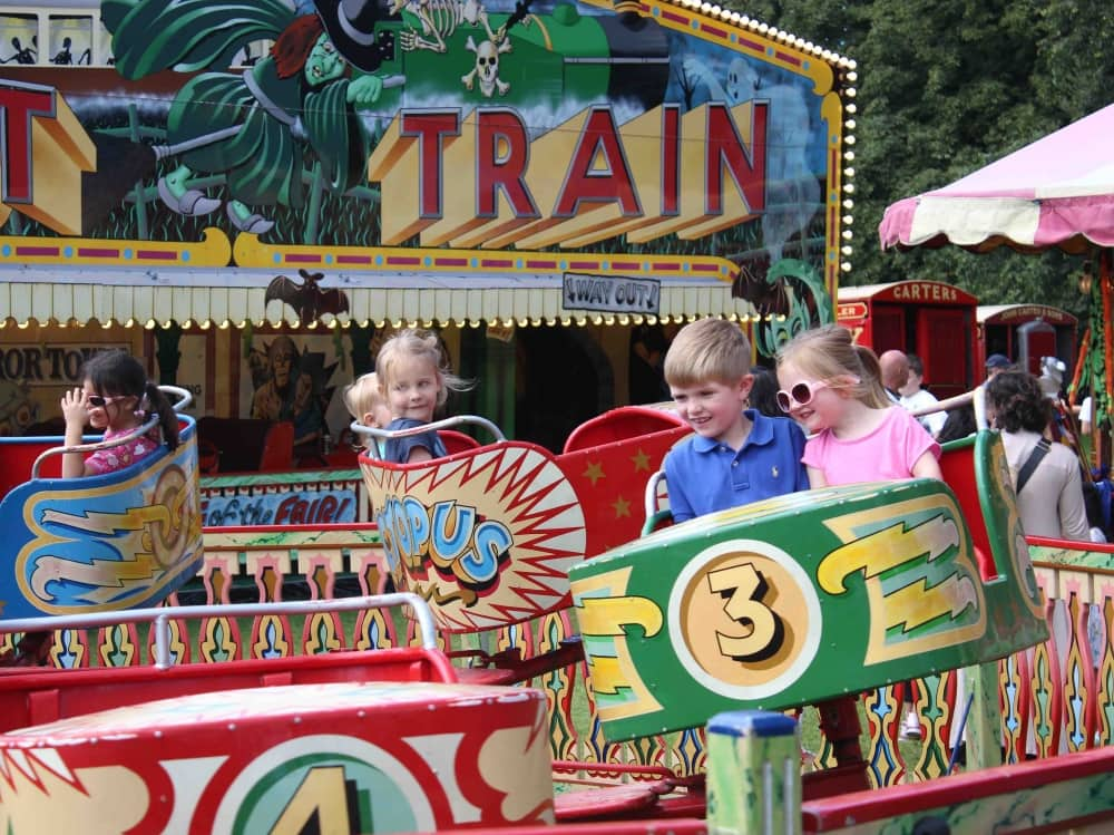 Carters Vintage fun fair ghost train and kids in spinning ride