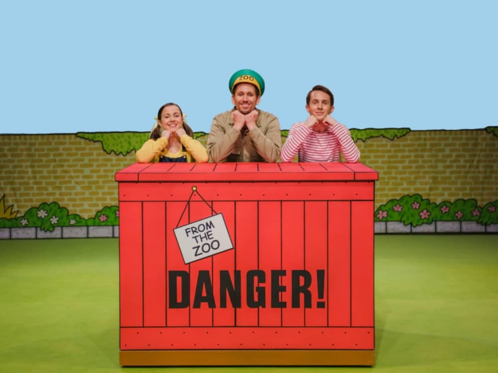 Dear Zoo stage show three actors lean on the red box delivery saying Danger from the the zoo