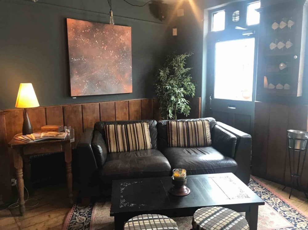 leather sofa, dark walls, modern art and plant in cosy snug area Eton mess pub eton Berkshire