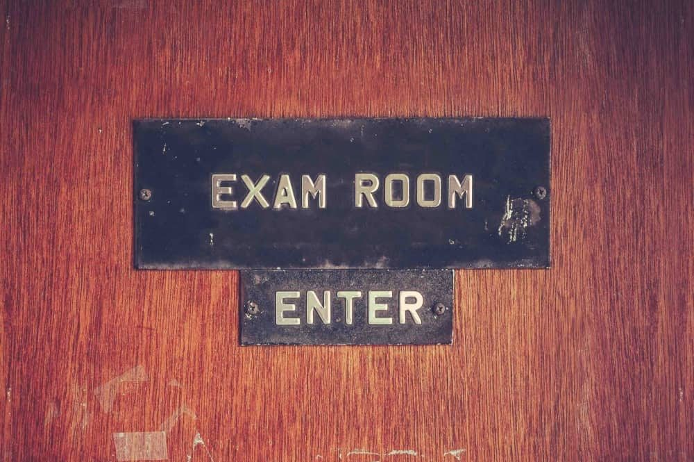 Marked wooden school door with metals sign Exam Room Enter
