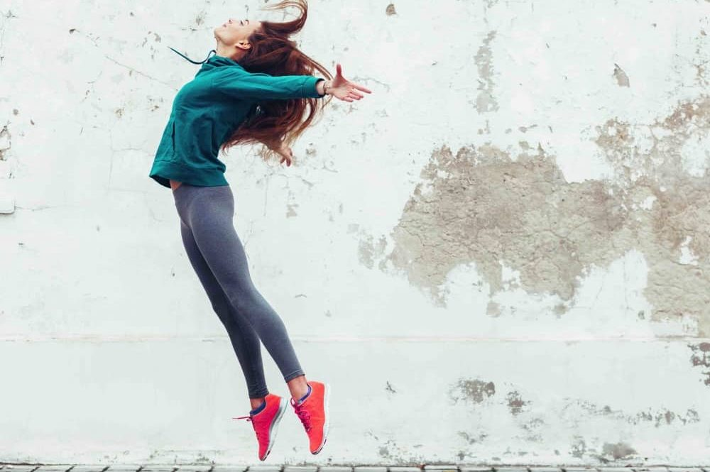 Girl jumping for joy in exercise gear by a shabby cream wall