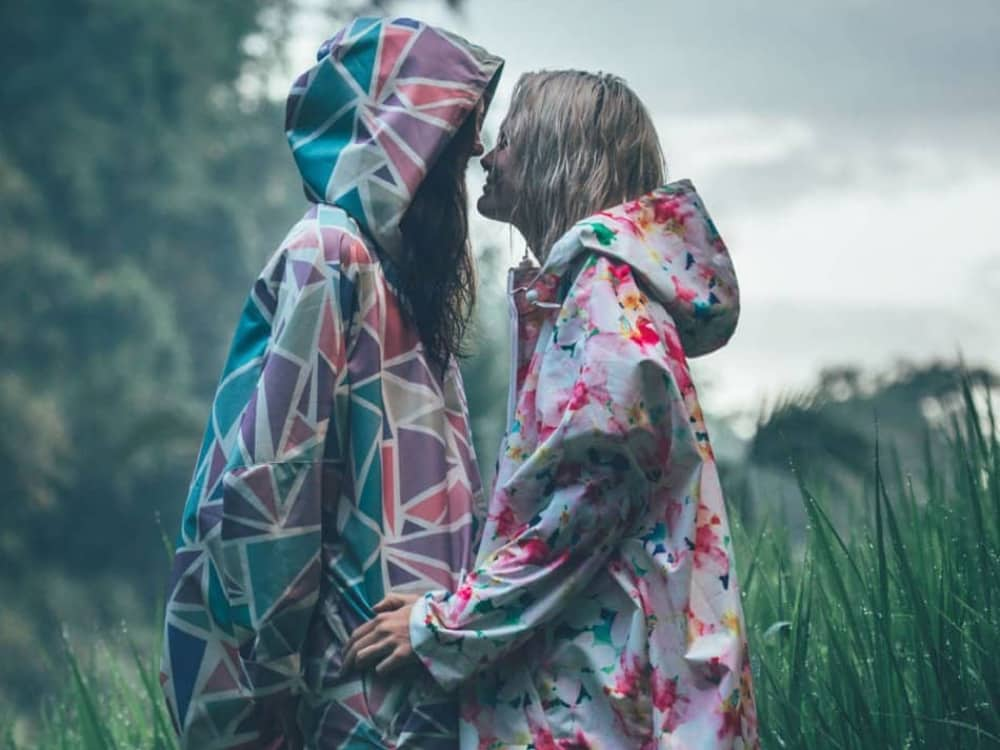 women standing in a field in the rain wearing Insane in The rain colourful graphic print rain macs