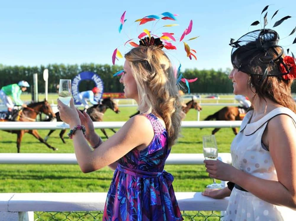 Stylish racegoers champagne flat racing Newbury racecourse