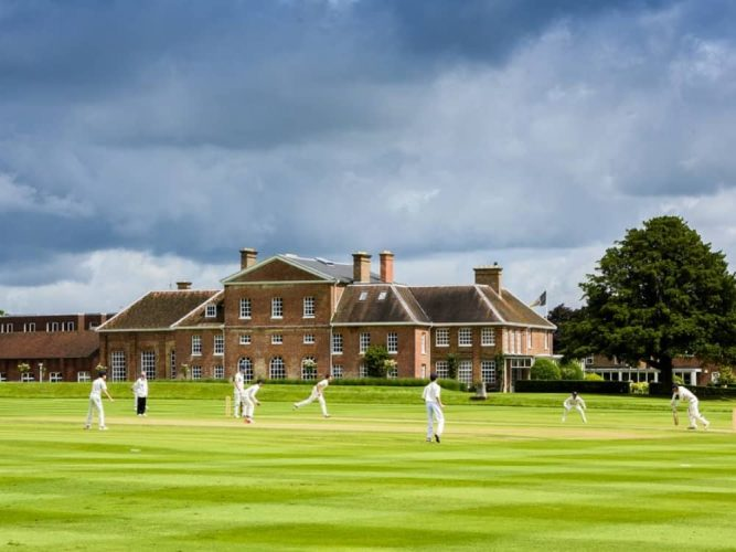 Dark skies over The Oratory school redbrick mansion and cricket green