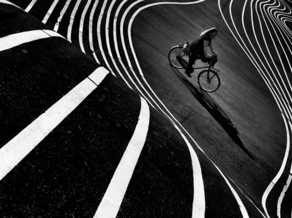 Woman on bike amid curving lines Tony Sellen photograph called Lines