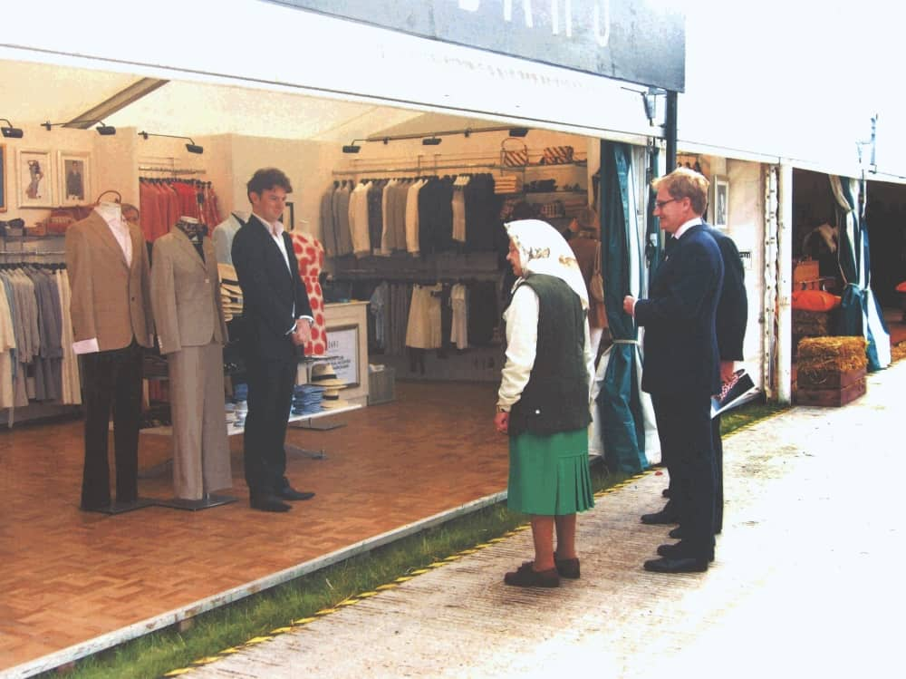 Queen Elizabeth wearing a headscarf gilet and green skirt shopping at the Royal Windsor Horse Show 2000