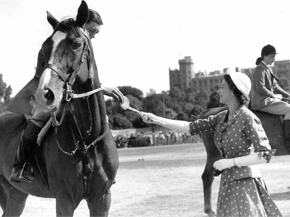 HRH Princess Elizabeth presents a rosette to rider in the gardens of Windsor Castle wearing a spotted two piece outfit and cream hat what gloves