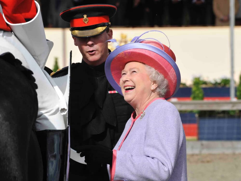 The Queen in lilac and pink laughing with household cavalry at Royal Windsor Horse Show