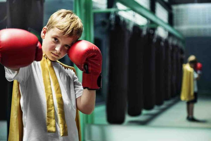 Positive strong boy in boxing gloves and a superhero cape