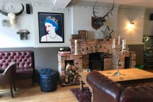 Cool artwork of the queen, wall mounted antlers and leather Chesterfield sofas at the Newbury Pub Berkshire