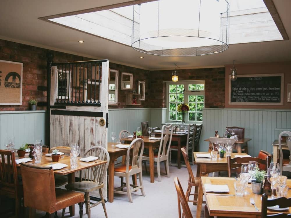 exposed brick walls, grey wood work, mix and match chairs and vintage wooden table Bunk Inn Curridge dining room with enormous chicken wire pendant light