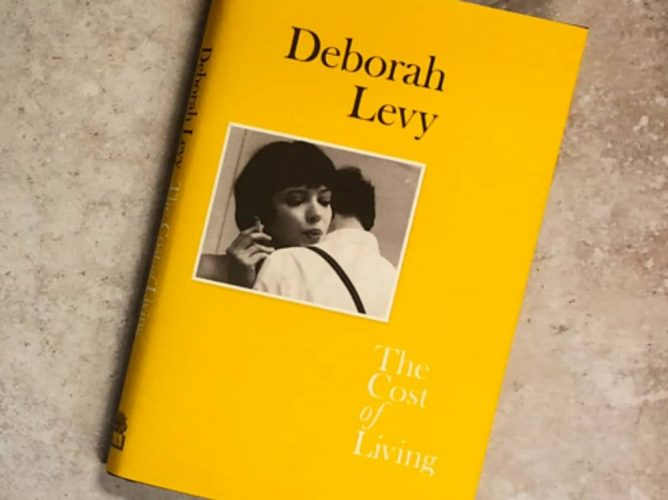 The Cost Of Living by Deborah Levy yellow book cover on polished cement table top