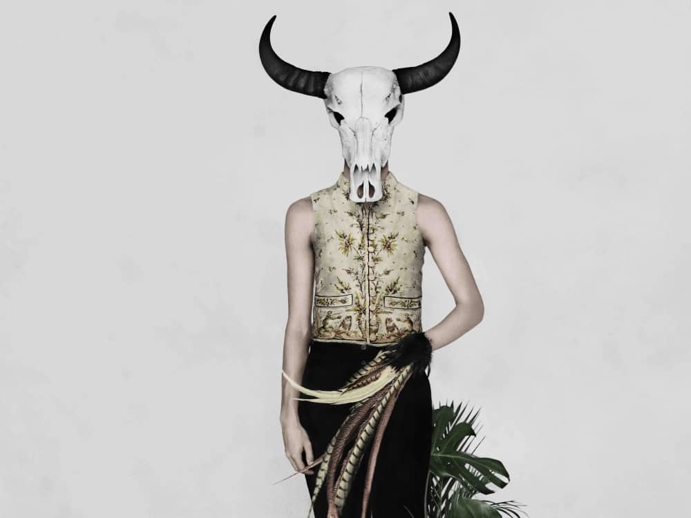 Model with bull skull wearing French embroidered waistcoat, black trousers, holding pheasant feathers – V&A Fashioned By Nature