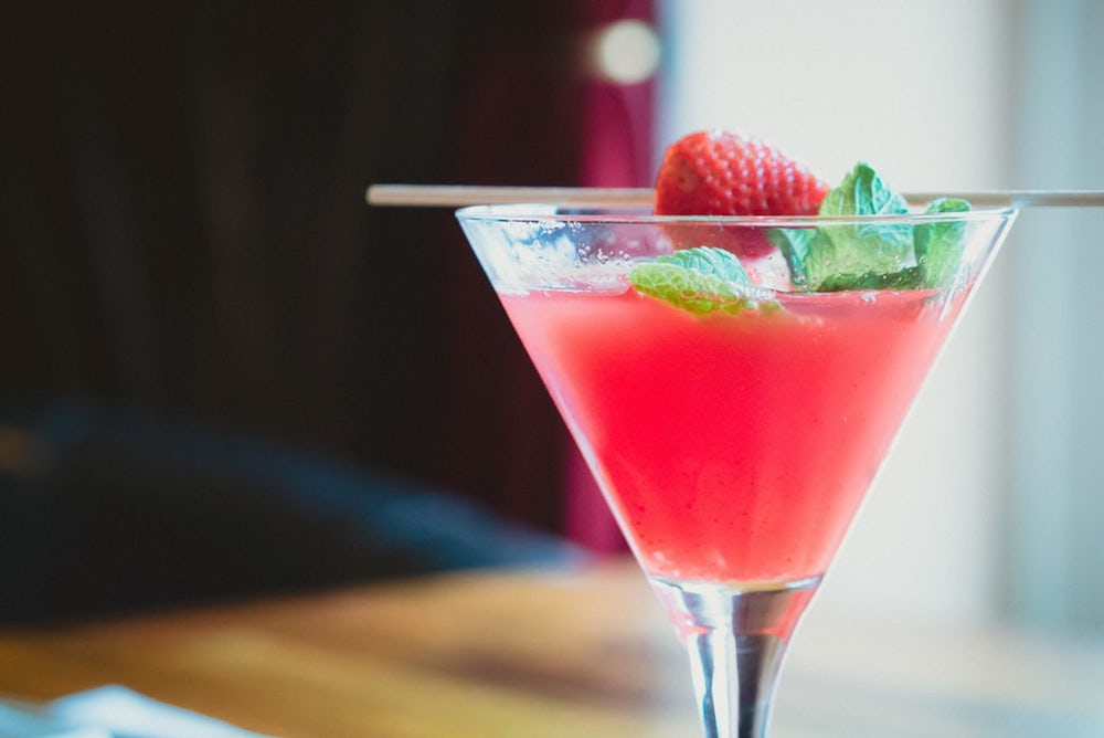 Pink cocktail in Martini glass wth strawberry and mint garnish