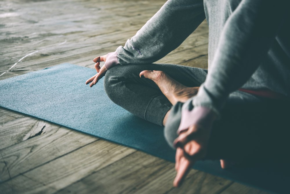 Yoga cross legged on mat in wooden floor studio