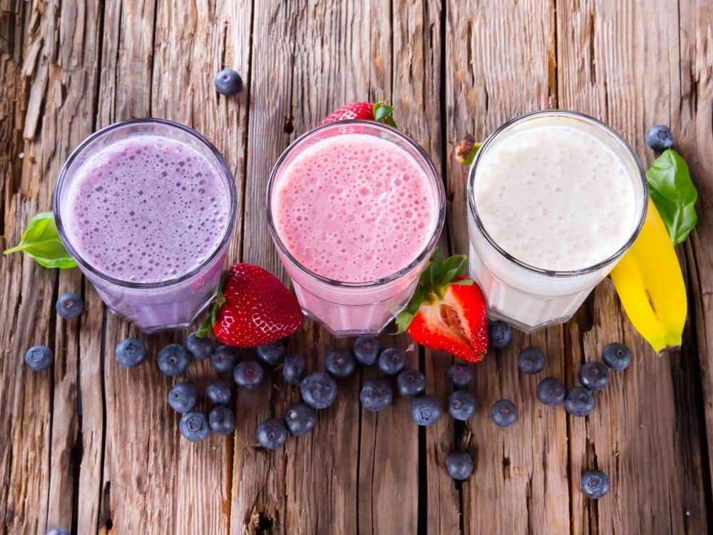 fruit smoothie in glasses wooden table strawberries and blueberries