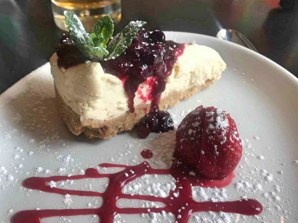 slice of vanilla cheese cake with berry compote and spring of mint The Boatman Windsor