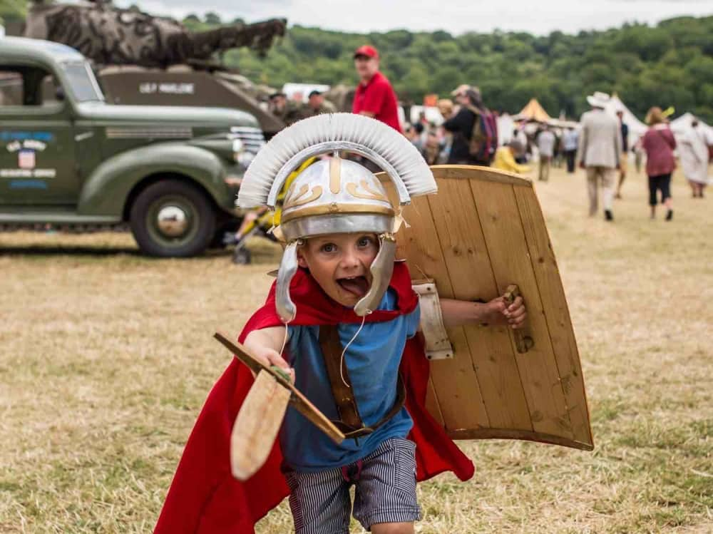 child dressed as roman soldier charging with wooden sword and shield at Chalke Valley History Festival Wiltshire