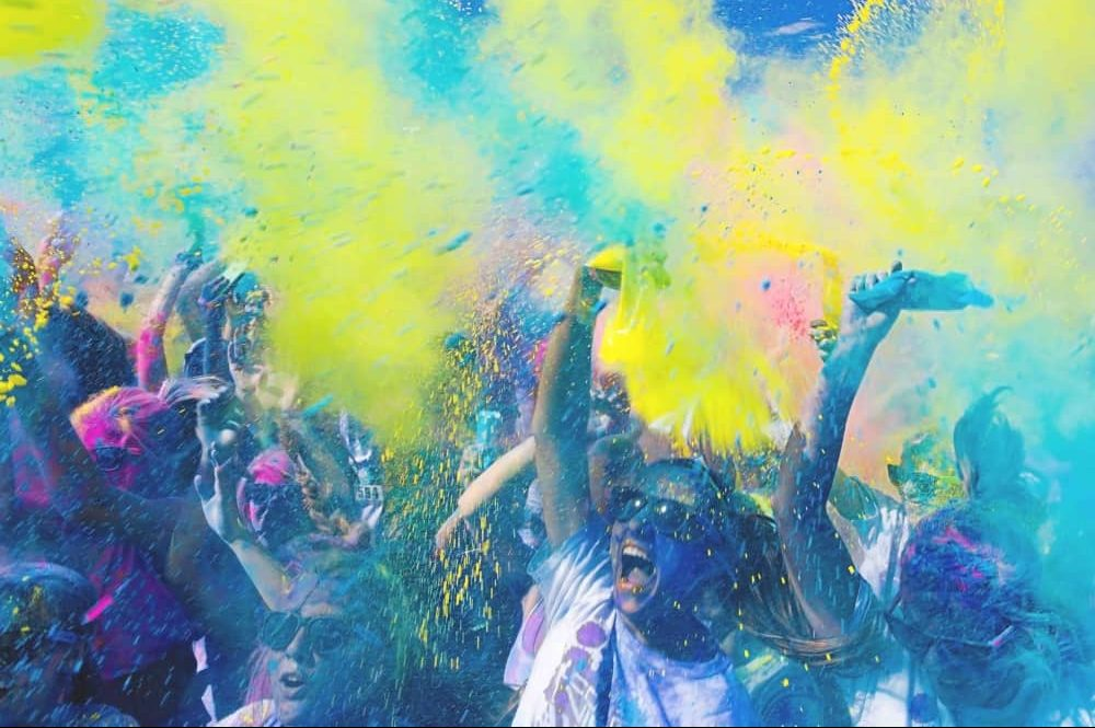 People partying at a festival throwing bright coloured powder in the air