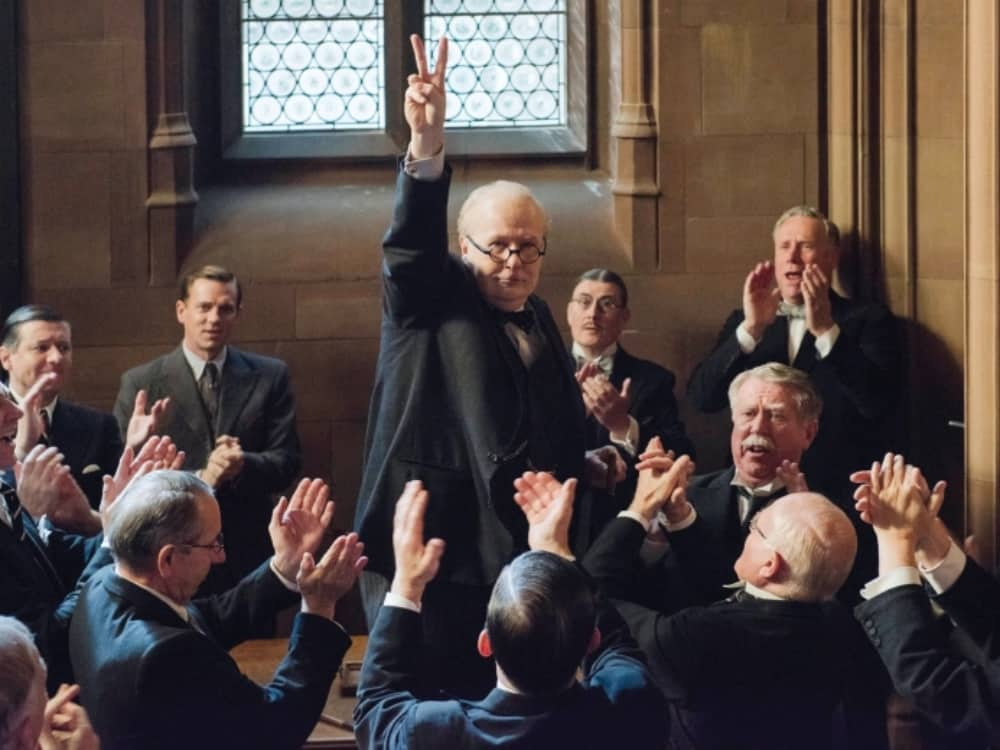 The Darkest Hour Gary Oldman as Winston Churchill V sign in front of applauding MPS