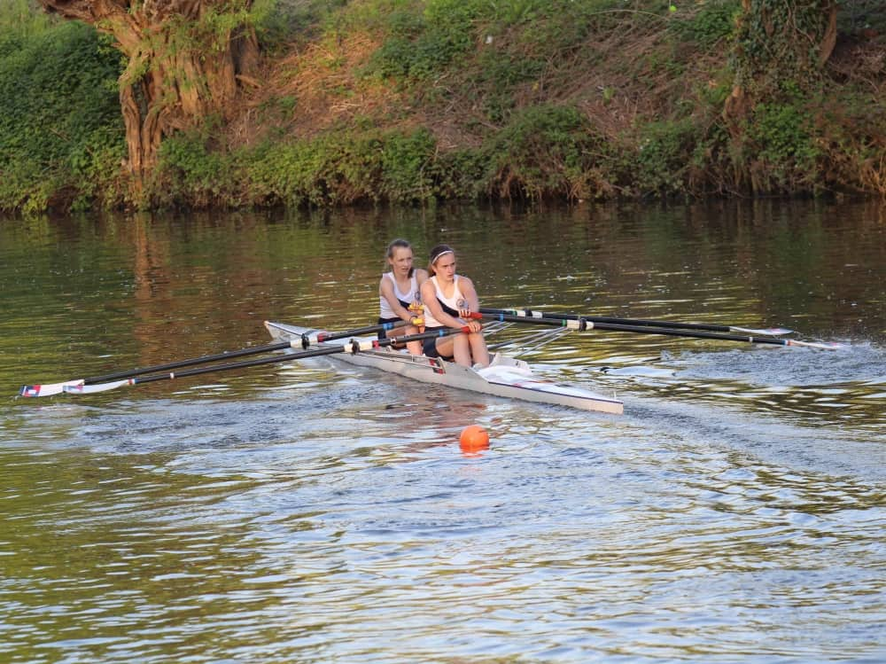 Two girls Pangbourne College rowing on the river Thames Berkshire