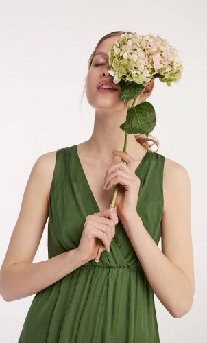 Woman wearing Hall Huber Green silk maxi dress carrying hydrangea