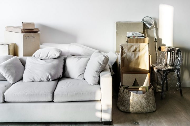 Moving house boxes full of belongs next to a light grey sofa