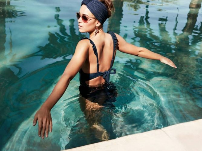 Modem in navy ruffle Accessorize swimsuit sunglasses and head scarf in swimming pool