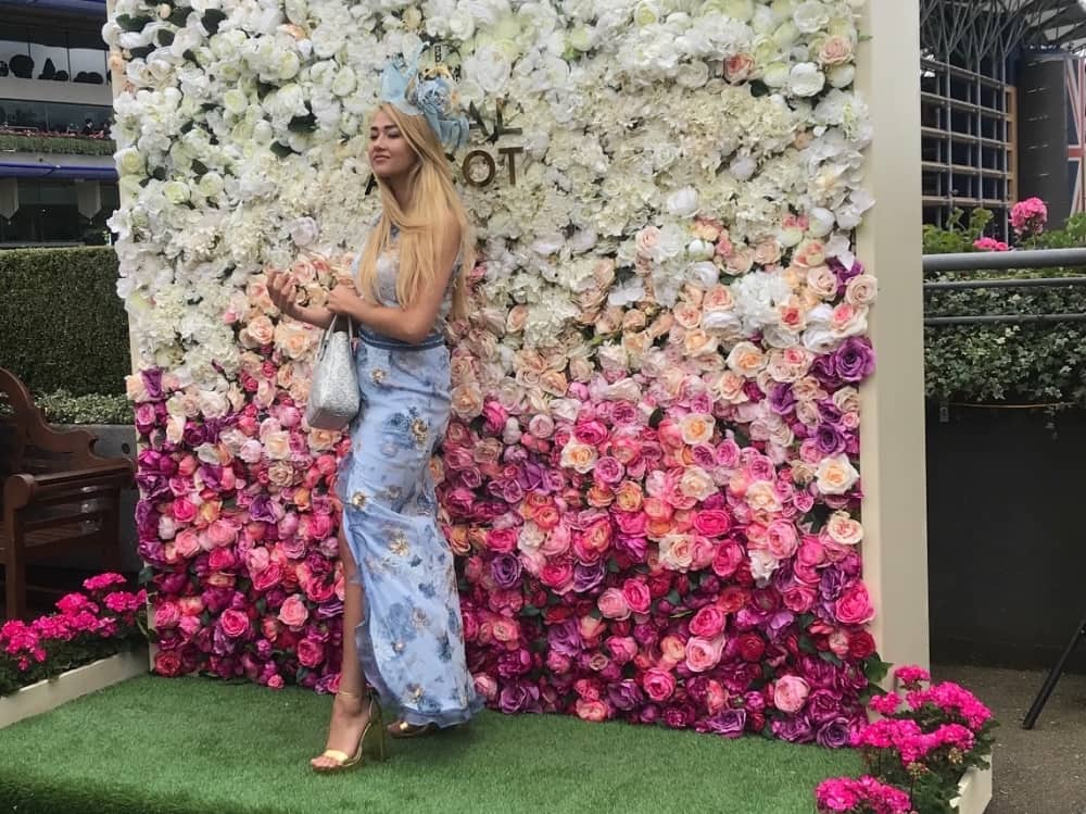 Royal Ascot 2018 pretty white and pink flower was with female racegoers in blue maxi dress and matching hat posing in front