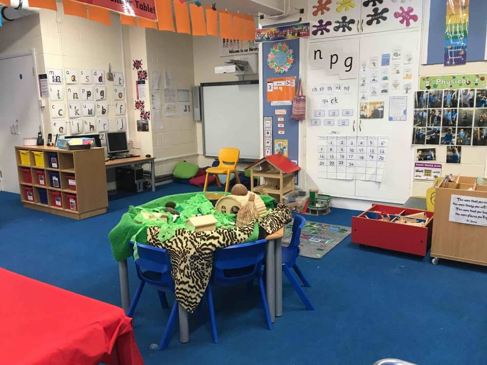 Highfield Prep School Maidenhead Berkshire large spacious nursery classroom with exploration table, bright floor cushions and artwork