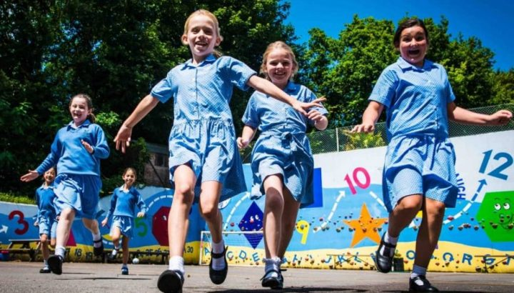 Highfield prep school girls in summer blue check dresses running across the netball court with street art climbing wall Maidhead Berkshire