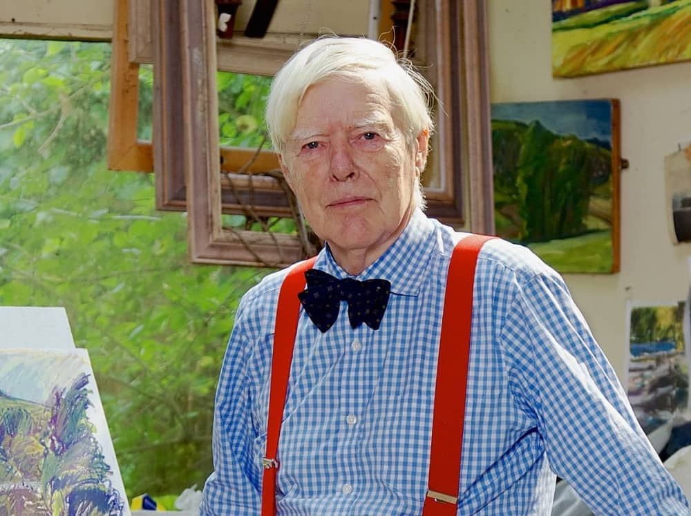 British artist Nick Schlee portrait wearing blue shirt bow tie and red braces