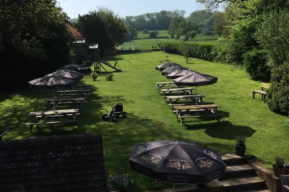Old Boot Stanford Dingley large garden play area, tables and parasols with countryside view